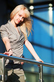 Young fashion woman against office windows — Stockfoto