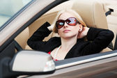 Happy young blond woman driving convertible car — Stock Photo