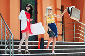 Two young fashion women with shopping bags — Стоковое фото