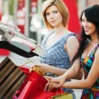 Two happy young women with shopping bags at the car trunk — Stock Photo