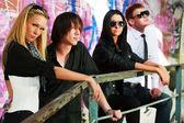 Young fashion people at the graffiti wall — Stock Photo