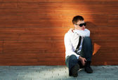 Young business man in depression sitting at the wall — Stock Photo