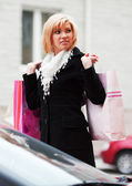 Happy young woman with shopping bags on the car parking — Stock Photo
