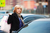Happy young woman with shopping bags on the car parking — Foto Stock