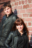 Happy young couple in leaher jackets at the brick wall — Stock Photo