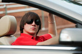Happy young man driving convertible car — Stock Photo