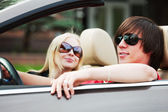 Happy young couple driving convertible car — Stock Photo