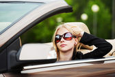 Happy young woman driving convertible car — Stock Photo