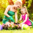 Mother and daughter planting flowers together — Stock Photo #40354285