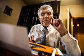 Ανώτερος άνθρωπος που γράφει σε μια γραφομηχανή — Φωτογραφία Αρχείου