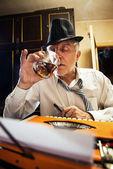 ретро старший мужчина писатель с бокалом виски — Стоковое фото