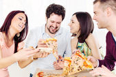 Cheerful friends eating pizza — Stock Photo