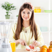 Young woman slicing Grapefruit — Stock Photo