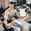 Personal trainer assisting a client — Stock Photo