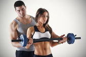 Personal trainer assisting a client — Stok fotoğraf
