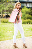Happy girl with shopping bags having a phone call — Stock Photo