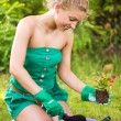 Young woman planting flowers — Stock Photo #42222397