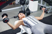 Young woman doing chest exercise — Stock Photo