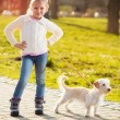 Little girl walking with her puppy dog in the park — Stock Photo #43259261
