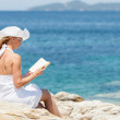Young woman reading book on the beach — Stock Photo #44508237