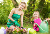 Beautiful mother and daughter planting flowers — Stok fotoğraf