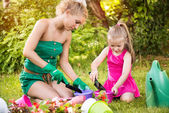 Beautiful mother and daughter planting flowers — Stockfoto