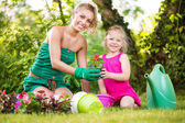 Mother and daughter planting flowers together — Stock Photo