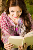 Girl with a book in the park — Stock Photo
