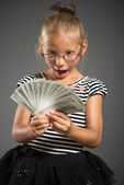 Little girl with money — Stock Photo