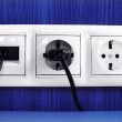 Plugs in electric and phone  socket. — Photo