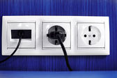 Plugs in electric and phone socket. — Stock Photo