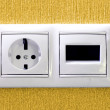 Plugs in electric and phone  socket. - Stock Photo