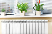 Heating white radiator radiator with flower and window. — Foto Stock