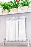 Heating white radiator radiator with flower and window. — Stock Photo