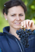 Woman showing red grape — Stock Photo