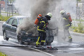 Firefighters are putting out a burning car — Stock Photo