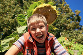 Happiness boy under sunflower. — Stock Photo