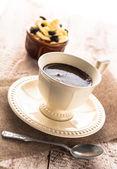 Tablero de madera dulce cremoso postre negro la taza de café — Foto de Stock