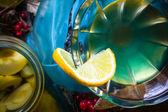 Alcohol quince liqueur sliced fruit jar wooden cups — Stock Photo