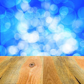 Blue bokeh background wooden table — Stock Photo