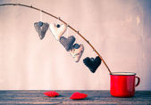 Heart hanging twig red cup — Stock Photo