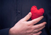 Closeup red heart hand man — Stock Photo