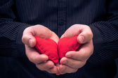 Two red hearts held male hands — Stock Photo