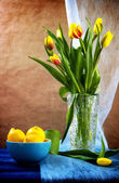 Still life bouquet tulips lemons — Stock Photo