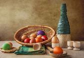 Still life colorful Easter eggs basket vase — Stock Photo
