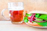 Delicious beef hamburger mug beer — Stock Photo