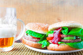 Two homemade grilled hamburger with cold beer — Stock fotografie