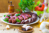Table plate sliced sausages vegetables — Stock Photo