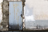 Ruined brick wall closed steel door — Foto Stock