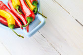 Background colorful peppers blue bowl — Stockfoto